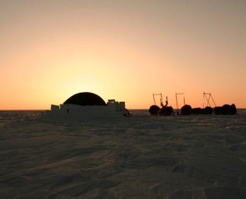 Tent in de sneeuw tijdens zonsondergang