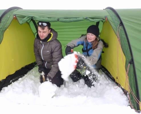 Voortent uitscheppen met sneeuw