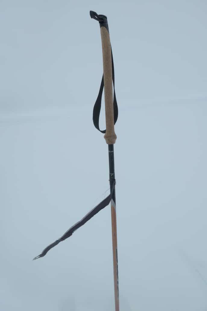 Een vlaggetje van vliegerstof aan de skistok